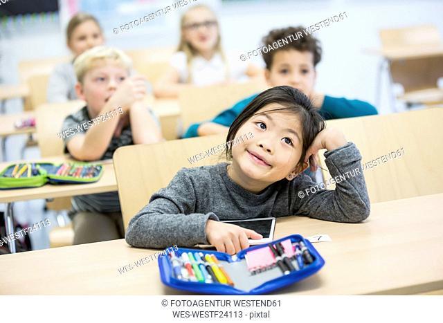 Portrait of schoolgirl with classmates in class