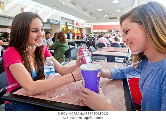 Two teens enjoying a break from shopping with a beverage