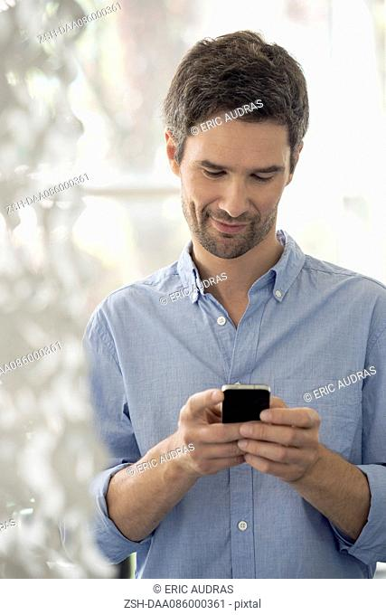 Man reading text message on cell phone