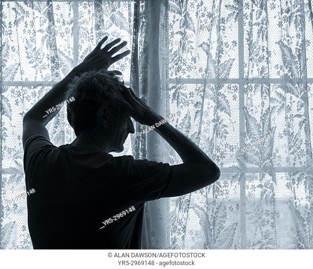 Mature man near window with hands on head. Mental health, male depression. . . concept image