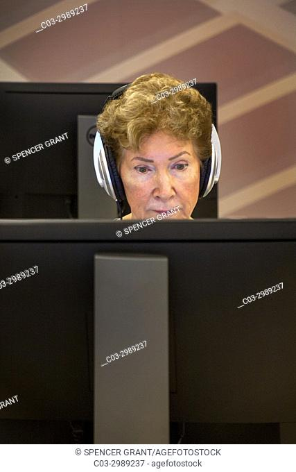 Wearing headphones, a senior woman looks at a computer monitor in a senior center computer class in Huntington Beach, CA