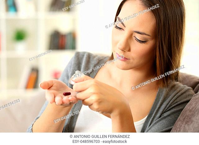 Woman extracting a pill from the blister sitting on a couch at home