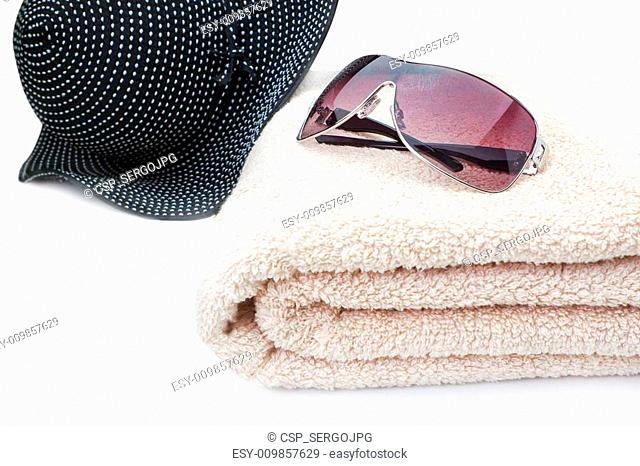 Glasses, a towel and a panama Beach Holiday. On a white background