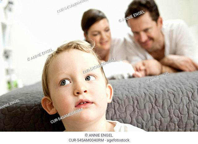 Boy sitting away from parents and infant