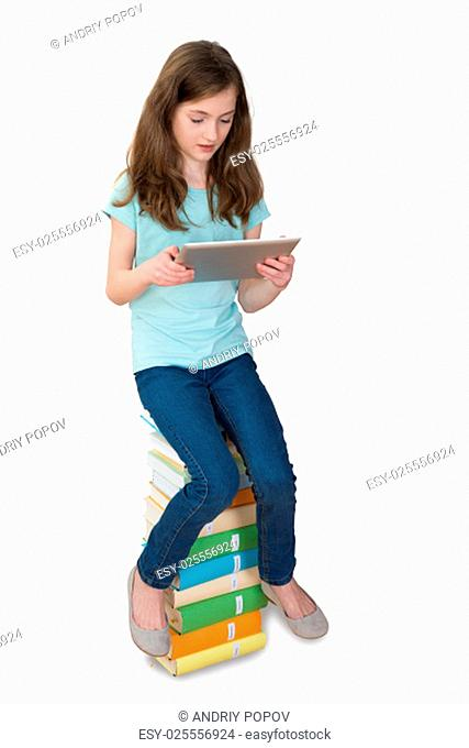 Girl With Digital Tablet Sitting On Multi-colored Stack Of Books Over White Background