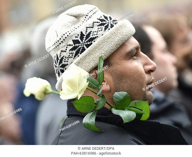A man wearing white roses on his jacket attends a commemorative rally held for the victims of the Paris terror attacks, at the Freiheitsplatz in Hanau, Germany