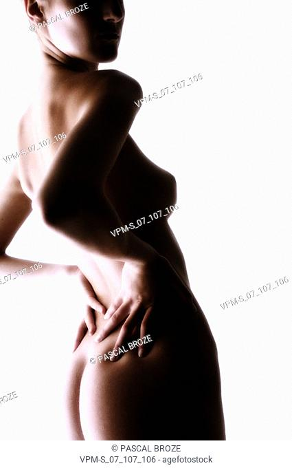 Side profile of a naked young woman standing with her hands behind her back