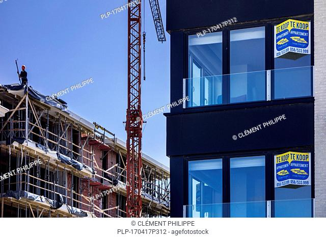 Apartments / flats for sale and construction crane at seaside resort along the Belgian North Sea coast, Belgium