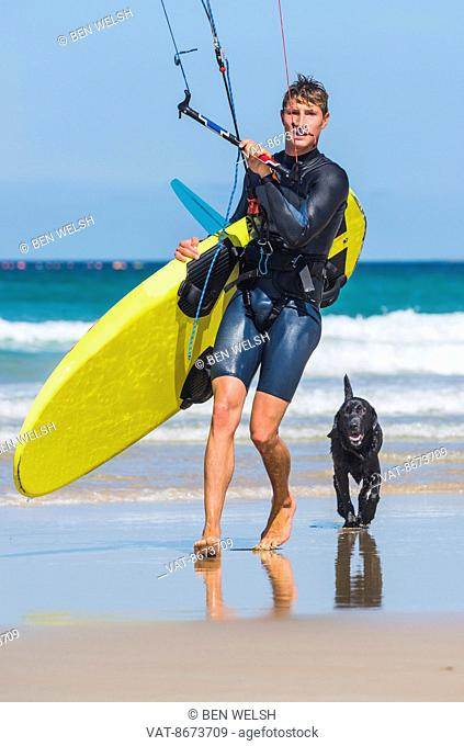 Kitesurfer walking on the beach with dog; Tarifa, Cadiz, Andalusia, Spain