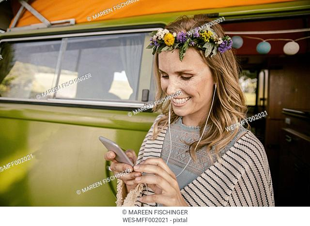 Hippie woman listening to music from her smartphone in front of van