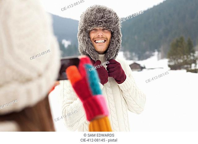 Woman photographing man wearing fur hat in snowy field