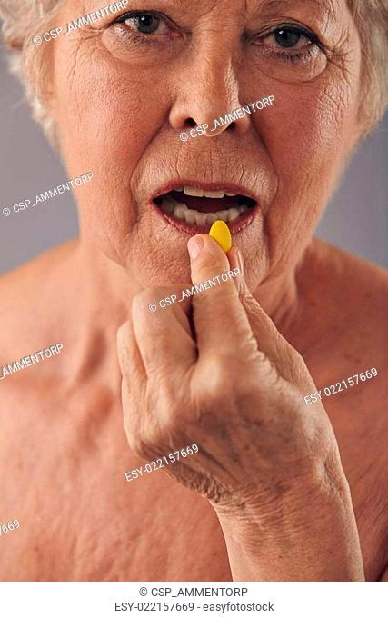 Mature woman talking medicine pill