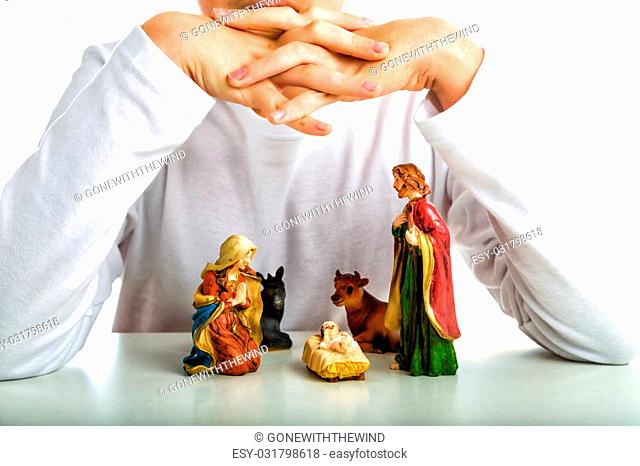 A boy put his hands as roofs and his arms as walls of the hut of a simple Christmas Crib where the little statues represent the Holy Family: the Virgin Mary