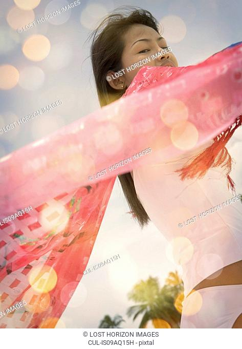 Close up of mid adult woman holding up pink scarf, Ari Atoll, Maldives