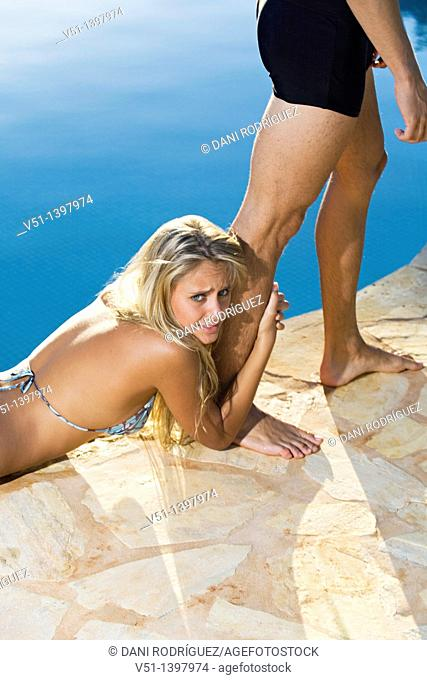 Young blonde girl grab the leg from a man by the swimming-pool