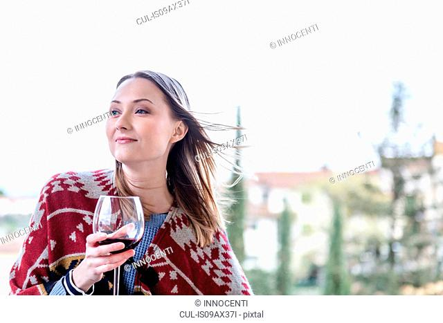 Woman holding glass of red wine looking away smiling
