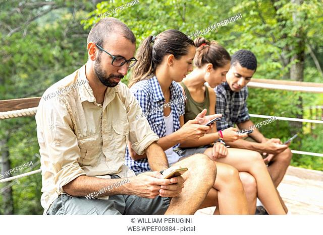 Italy, Massa, hikers in the Alpi Apuane mountains looking at their smartphones and sitting on a bench