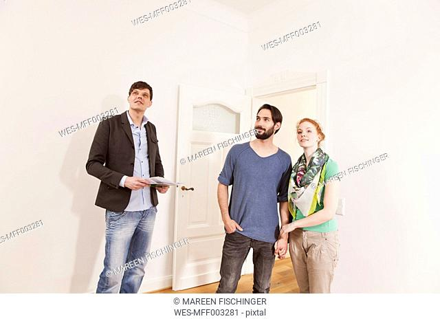 Real estate agent showing a couple around in a new apartment
