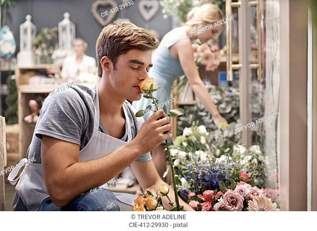 Florist smelling rose in flower shop