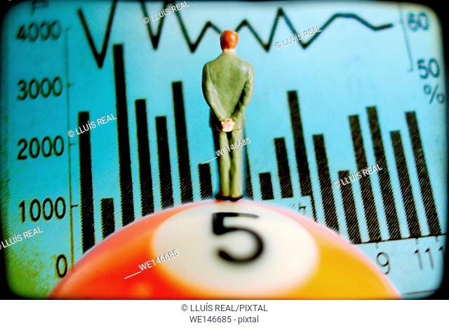 figure of a executive on top of a billiard ball with number 5 watching an economic graph