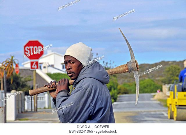 black roadworker with a pickaxe over the shoulder, South Africa, Arniston