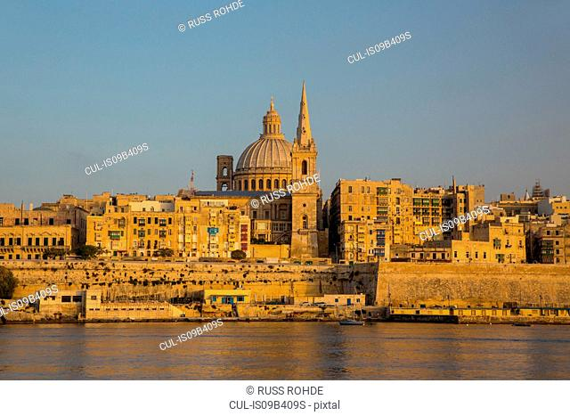 Dome of carmelite church and St. Paul's Cathedral over water, Valletta, Malta