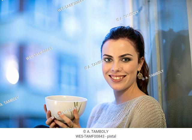 Portrait of smiling young woman with tea bowl in front of window