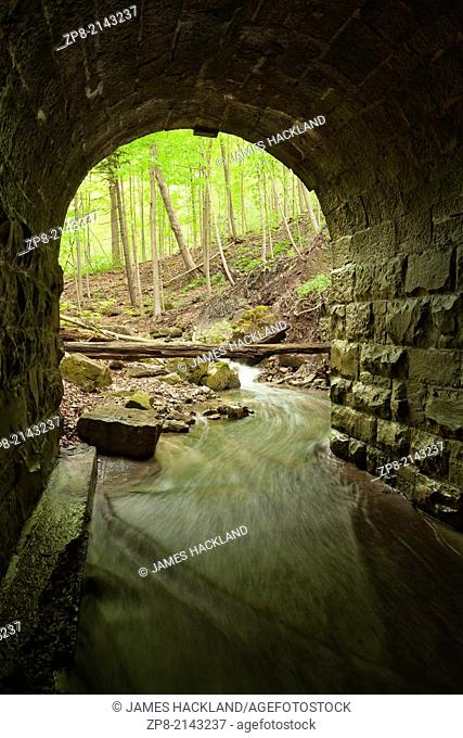 The entrance of a lovely stone block culvert looking out towards the forest in Tiffany Falls Conservation Area, Hamilton, Ontario, Canada