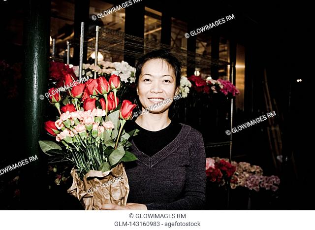 Woman holding a bouquet of flowers at a flowers market, 28 Street, New York City, New York State, USA