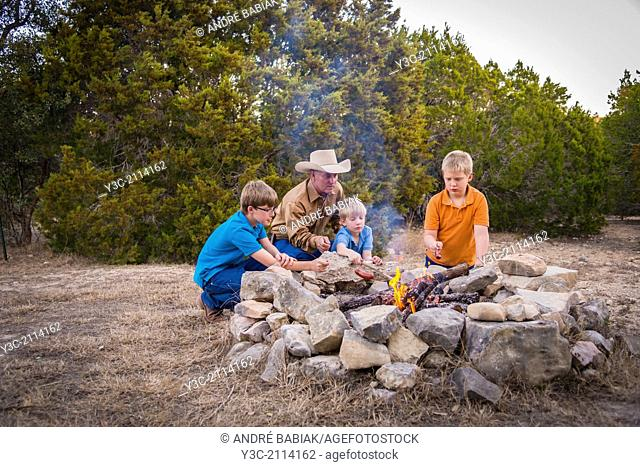 American man with his three boys having a good outdoor adventure time when they are roasting sausages over a camp fire
