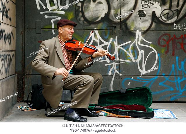 Elderly violinist playing for tips on a street in Florence, Italy. The graffiti on the wall behind is quite in contrast to the impeccable formal attire of the...