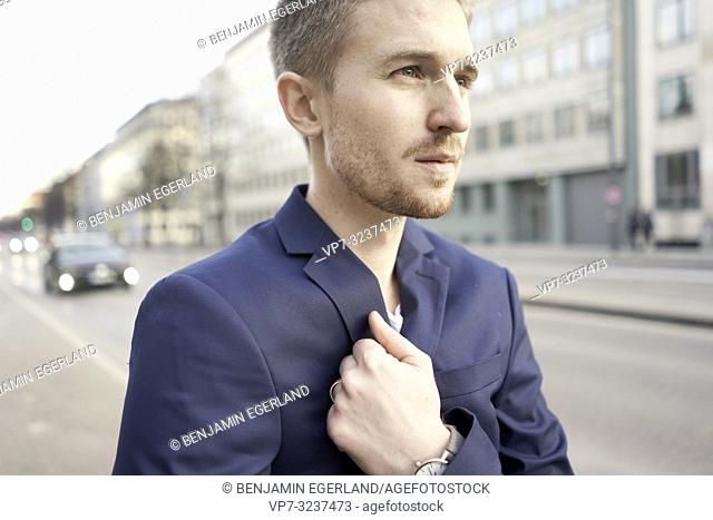focused young business man at street, wearing blazer, in city Munich, Germany