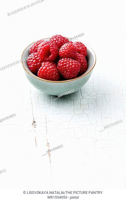Raspberries in bowl on blue background