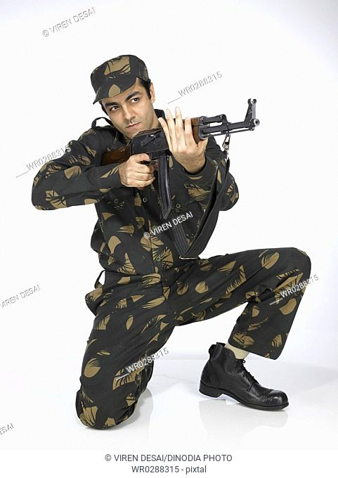 Indian army soldier sitting on knee pointing AK-47 gun MR702A