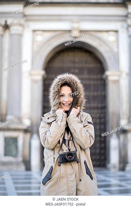 Spain, Granada, portrait of happy young woman with camera outdoors