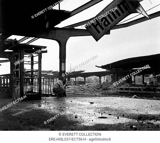 U.S. soldier crouches at the railroad station in the newly captured town of Hamm, Germany. April 6, 1945. World War 2. (BSLOC-2014-8-74)