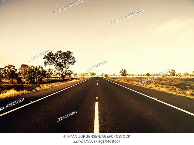 Long vast stretch of Australian rural road leading through arid bushland. Mirrool, northern part of the Riverina region of south-west New South Wales, Australia