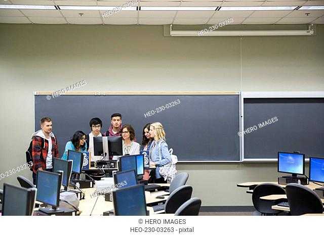 Professor and students around computer in classroom