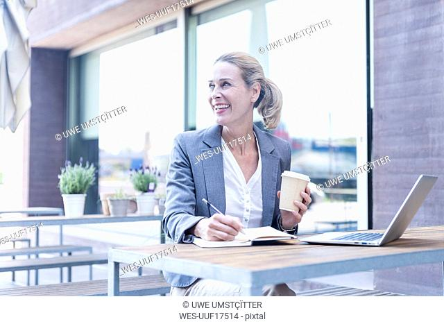 Happy businesswoman working at an outdoor cafe