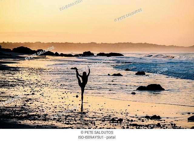 Silhouetted female ballet dancer poised on one leg at sunset on beach, Los Angeles, California, USA