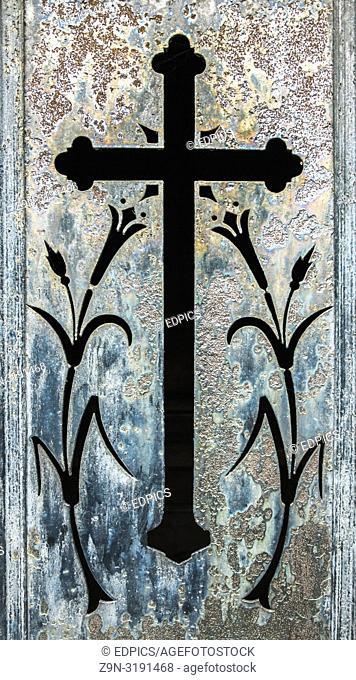 historic metal door showing a cross and floral ornaments, paris, ile de france, france