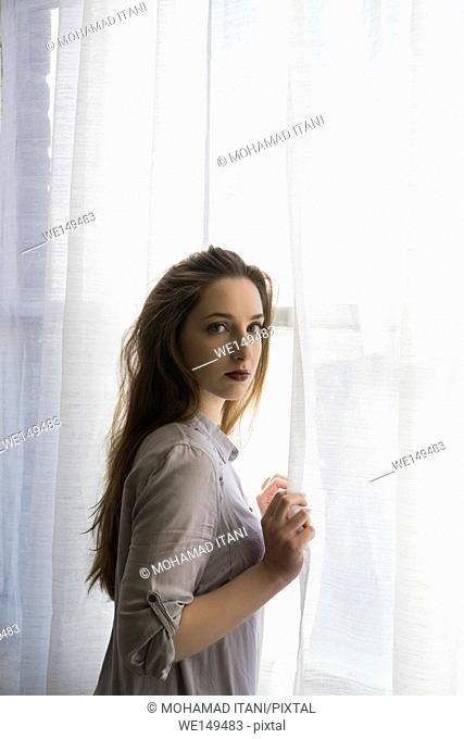 Beautiful young woman standing by the window