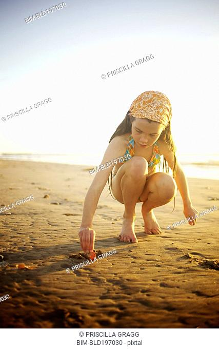 Mixed race girl digging in sand on beach