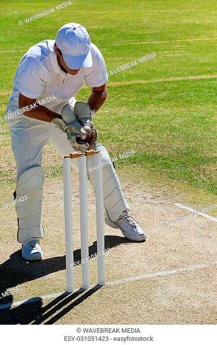 Full length of wicketkeeper catching ball behind stumps on field