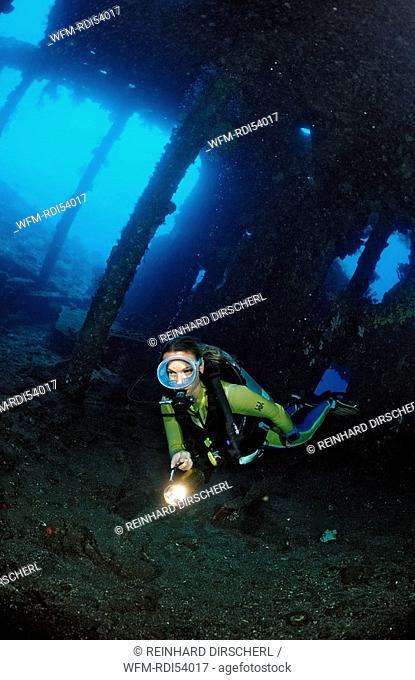 Scuba diver examines ship wreck Liberty, Bali Tulamben Indian Ocean, Indonesia