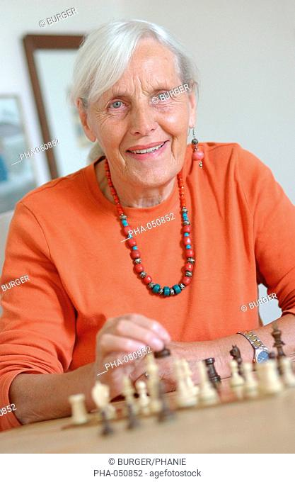 A 80 years old woman playing chess. Practising a cerebral activity reduces memory loss of elderly persons