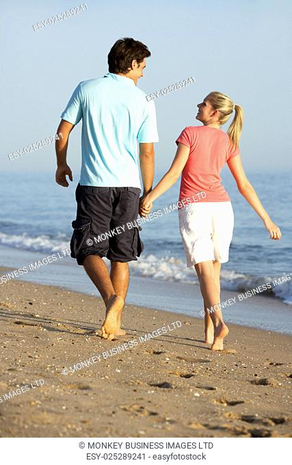 Young Couple Walking Along Beach