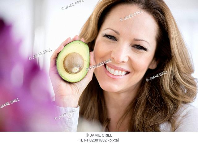 Portrait of woman holding avocado