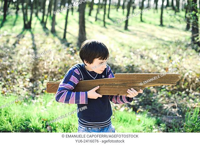 Child plays with a shaped wooden rifle