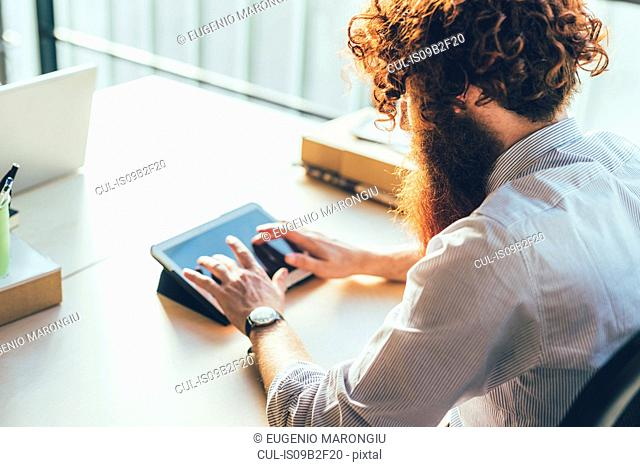 Young male hipster with red hair and beard using digital tablet touchscreen at desk